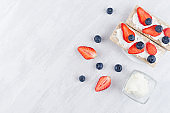 Fresh summer fruit healthy appetizer of whole grain rye crisps breads with ripe strawberry slices, blueberry, sweet cream cheese on white wood board, top view, copy space.