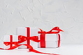 Gentle white gift boxes with red silk bow on wood table in white interior as festive anniversary background.