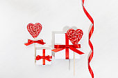 Fun Valentine's day background - white gift boxes with red bow, sweet lollipops hearts on white wood board.