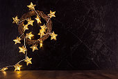 Fashion christmas background with gold glowing lights with stars on brown natural wreath of twigs on black wall and wood board, copy space.