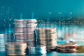 Double exposure of city and stack rows money coin with trading graph chart stock market.
