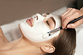 Beautiful young woman receiving white facial mask in the beauty salon. Spa skin and body care. Facial beauty treatment.