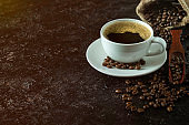 Hot black coffee for morning beverage menu in white ceramic cup with coffee beans roasted in burlap sack bag on dark grunge rustic table background. Flat lay with copy space.