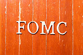 Alphabet letter in word fomc (abbreviation of federal open market committee) on old red color wood plate background