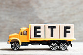 Truck hold letter block in word ETF (abbreviation of Exchange Traded Fund) on wood background