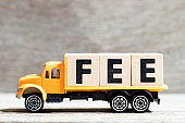 Truck hold letter block in word fee on wood background
