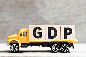 Truck hold letter block in word GDP (Abbreviation of good distribution practice or gross domestic product) on wood background