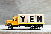 Truck hold letter block in word yen on wood background