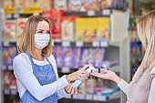 Adult woman in medical mask using hand sanitizer before shopping for groceries