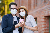 Adult romantic couple wearing masks on the walk in the city