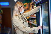 Adult woman in medical mask shopping for groceries