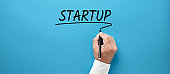 Businessman hand writing the word startup on blue background. Business start up