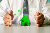 House model and energy icon in male businessman hands, energy-saving home, and housing loan concept.