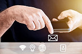 Male person holds a smartphone in his hand with his finger touching towards the mail icon. Online assistance or support concept.