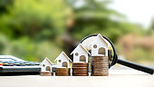 House model on a pile of coins and blurred natural green background. Real Estate Investment Ideas Mortgage and home building interest rates