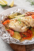 Foil with baked fish and vegetables.