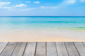 Wooden terrace on beautiful beach, summer weather and holiday concept
