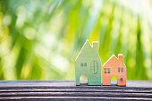Miniature wooden house over blurred green leaves background