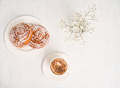 Cinnabon buns. Cinnamon rolls with spices and apple filling and cup of cappuccino on white background. Swedish or American breakfast.