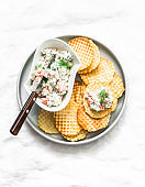 Crispy potato waffles and salmon, cream cheese, cucumber spread on a light background, top view. Delicious appetizer, tapas
