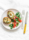 Roasted potatoes stuffed spinach and mozzarella on a light background, top view. Delicious tapas, snack, appetizers