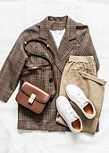 Women's plaid jacket, jogger pants, white leather sneakers, bag - women's fashionable comfortable clothing on a light background, top view