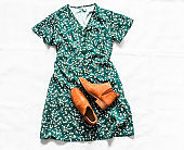 Women's clothing for spring, summer, autumn - floral dress, suede chelsea boots on a light background, top view