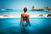 summer vacation time - back view of caucasian blonde in bikini on blue lagoon white sand beach