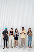 Happy group of multicultural friends using smartphones against white wall