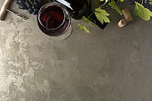 Red wine and grapes. Wine and grapes in a vintage setting with corks on a wooden table. Top view.  Copy space of your text.