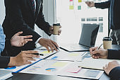 hand holding pen, businesswomen and businessmen team meeting to plan strategies to increase business income. Have a brainstorming finance graph analysis and discussing for the new target success