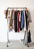 Rack with colorful clothes on hangers over white brick wall background