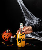 Scary colorful Halloween cocktail with party decorations on dark background with copy space