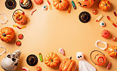 Halloween holiday decorations with pumpkins and candies top view on orange background