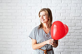 Young woman holding read heart shaped balloon on white brick wall background