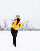 Happy beautiful woman playing outdoor, trying to catch snowflakes with her tongue