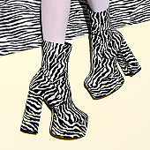 Fashion legs in heel party zebra boots on  minimal background. Animal texture print. Stylish tropical concept
