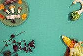 Autumn minimalist mock- up scene. Fall winter Decor mushrooms, corn, pumpkin and leaf on green plate and paper  background. Seasonal concept.  Stylish flat lay banner