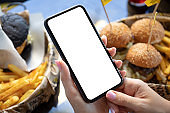 female hands holding phone with isolated screen background of burgers