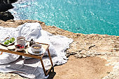 Beautiful festive breakfast with seascape view on the brink of a precipice. Travel and healthy lifestyle concept.