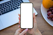 female hand holding golden phone with isolated screen in office