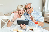 Happy older couple using computer tablet together at home, excited mature man and woman looking at mobile device screen, video call chatting online while having breakfast at home.