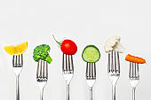 Fruit and vegetable of silver forks against a white background concept for healthy eating, dieting and antioxidant