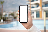 male hand holds phone with isolated screen on city background