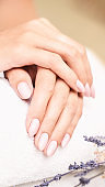 Classic pink wedding nail manicure on white backdrop. Spa treatment concept