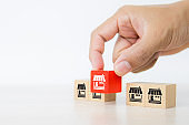 Hand choose cube wooden toy blocks stacked with franchise business store icon