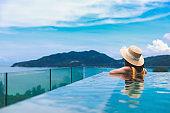 Asian travel bikini woman relax in infinity pool resort on phuket beach Thailand