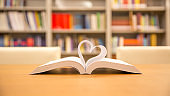 Close up page of book in heart shape at library