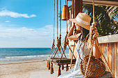 Traveler asian woman travel and relax on swing in beach cafe at Koh chang summer Thailand
