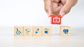 Hand choose medical bag icon on cube wooden toy blocks stacked with other medical symbols